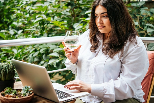 A woman sitting on her balcony outside, enjoys a glass of wine during a virtual wine tasting on her computer.