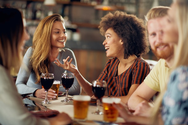 Friends chatting and drinking alcohol while  sitting at restaurant. Multi ethnic group.