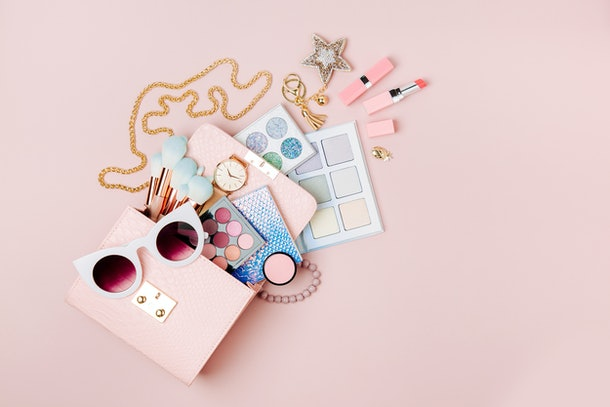 Cosmetic products flowing from Makeup bag on pastel pink background.  Flat lay, top view. Fashion concept