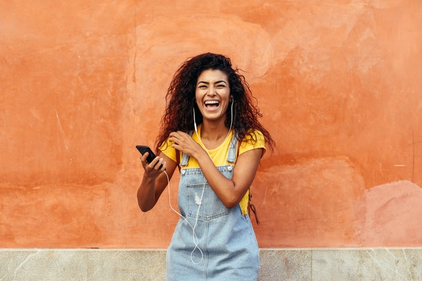 A girl in overalls and a yellow T-shirt laughs while holding her phone outside in front of an orange wall.