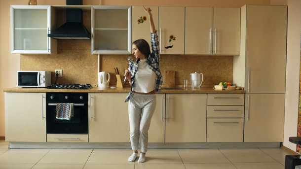 A woman in sweats dances in her bright kitchen.