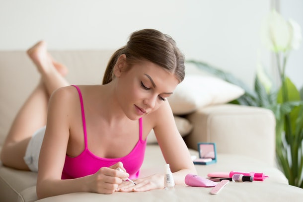 Young woman applying lacquer by brush from bottle, polishing painting fingernails with colorless protective enamel while lying on sofa, doing french manicure at home, perfect healthy nails care