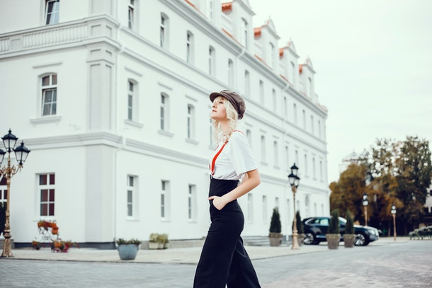 A fashionable woman stands in the streets of London near a white building.