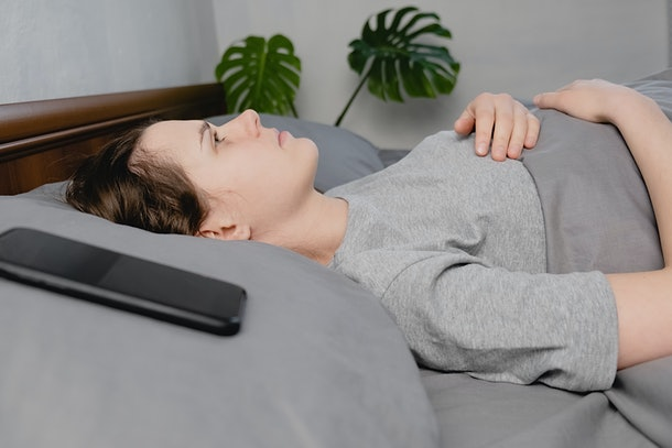 Young frustrated woman lying down on bed with phone looks into the ceiling, waiting message feels unhappy anxious having problems relations difficulties. Thinking about divorce break up concept