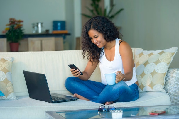 lifestyle portrait of young happy and beautiful black afro American woman using internet texting on mobile phone while working on laptop computer at home living room sofa couch relaxed