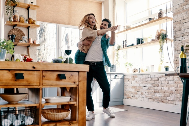 A trendy couple laughs and dances in a bright kitchen.