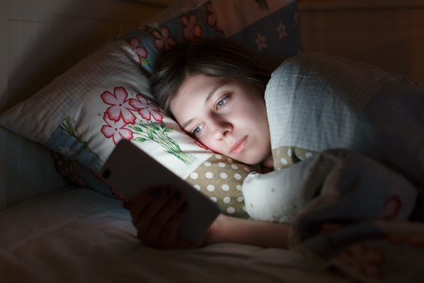 Young sleepy tired girl lying in bed using smartphone at late night, can not sleep. Social media addiction, dependency on cell phone, insomnia, nomophobia, sleep disorder, sleeplessness concept.
