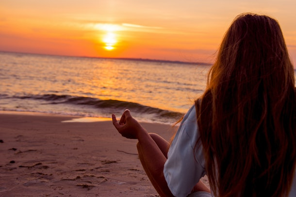 Girl is engaged in yoga on the beach. girl is meditating. Girl with long hair sitting on the beach. Girl meditating at sunset. Evening meditation near the ocean