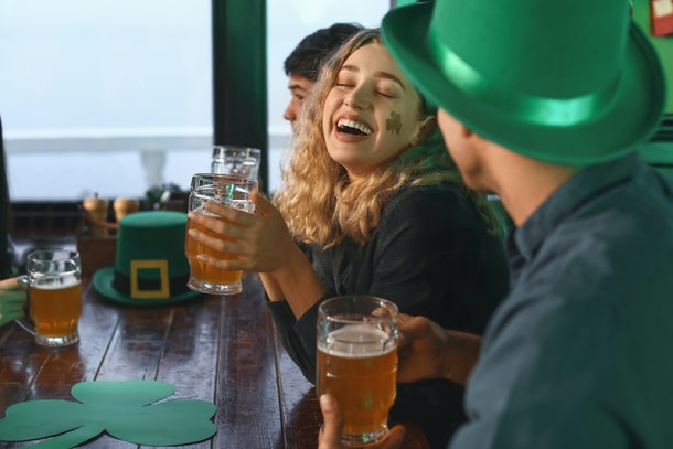 A woman with a shamrock sticker on her cheek laughs while celebrating St. Patrick's Day with friends at a bar.
