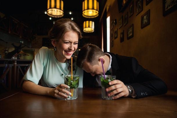 A man and woman hold mojito glasses and laugh at a bar.