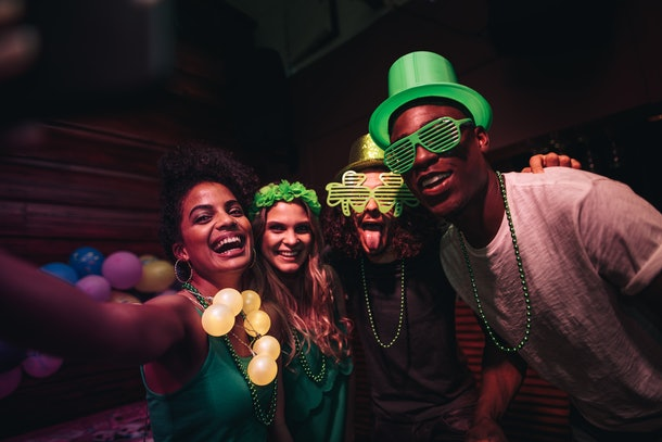 A group of friends smiles for a selfie and celebrates St. Patrick's Day at a bar.