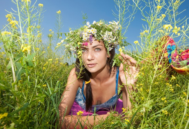 girl in a flower wreath lies in the grass