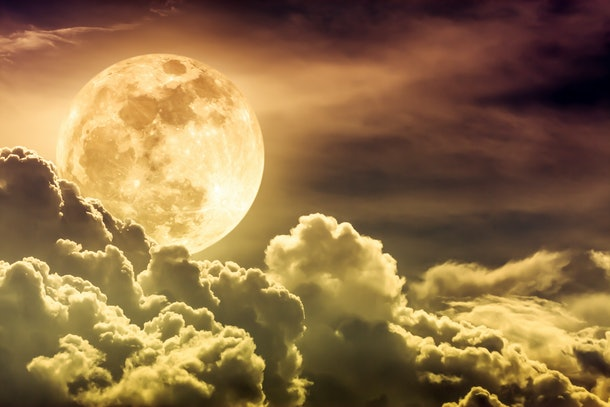 Attractive photo of gold background nighttime sky with clouds and bright full moon with shiny. Nightly sky with beautiful full moon behind cloud. Outdoors at night. The moon were NOT furnished by NASA