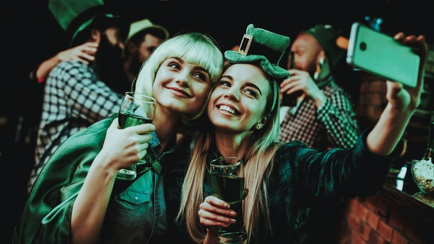 Two girls smile and snap a selfie at a pub on St. Patrick's Day.