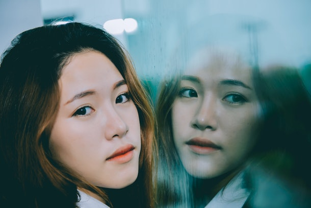 Closeup asian woman sad from love at mirror with reflection in a raining day vintage style,heartbreak woman concept,stress girl