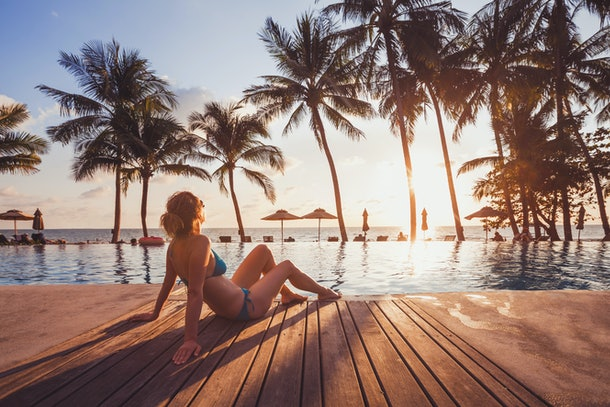 tropical getaway retreat in luxury beach hotel, luxury travel, woman relaxing near swimming pool at sunset