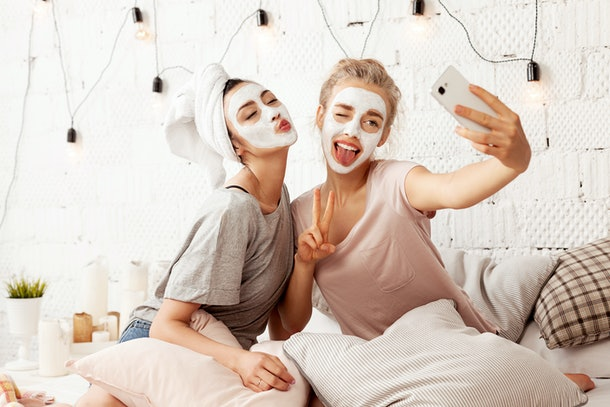 Portrait of cute young women sending kisses smiling sweetly and making amusing faces for picture. Cheerful lovely friends taking selfie at home with facial cosmetic mask. Skincare concept