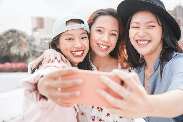 Three women smile and take a selfie outside.