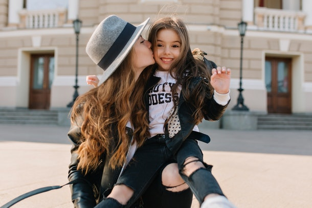 A stylish woman wearing a leather jacket kisses her niece.