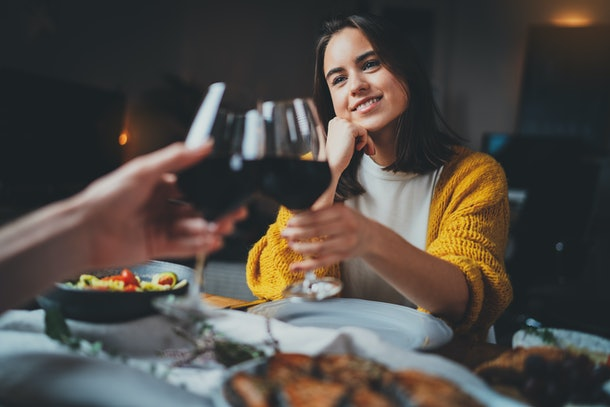 Romantic couple dating at night in restaurant, cozy atmosphere, beautiful young couple making cheers with glasses of red wine during romantic dinner, Sweet Couple Date Dinner