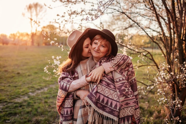 A mother and adult daughter hug in the park next to a cherry blossom tree on a sunny spring afternoon.