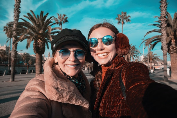 Mother and adult daughter snap a selfie with palm trees in the background, bundled up in trendy jackets.
