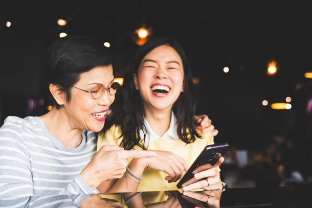 An asian mother and daughter laugh and smile while looking at a cell phone in a restaurant.