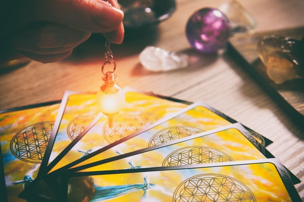 Tarot cards dowsing tool in hand and crystals as a concept of psychic advisor or ways of divination