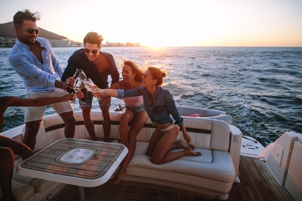 A group of friends toast their wine glasses on the back of a yacht at sunset in the summer.