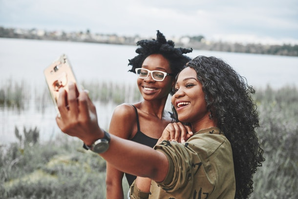 Two female friends smile and pose for a selfie outside on a summer day by the water.