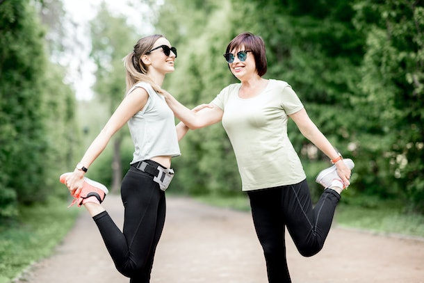 A mother and daughter stretch in a park during an afternoon run.
