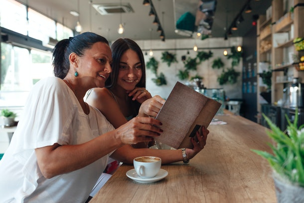 Mother and daughter drink coffee and look at a cafe menu.