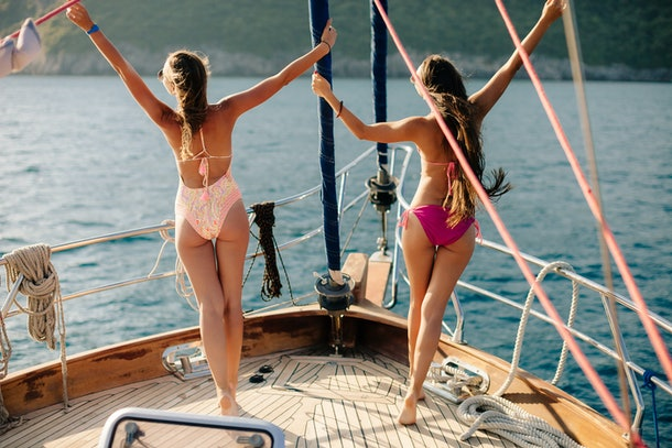 Two women pose at the front of a sailboat in their bathing suits at sunset.