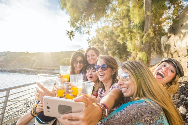 A group of women hold up cups of orange juice while snapping a selfie by the water on a sunny day.
