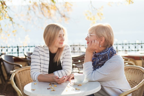 A mother and daughter look at each other and smile while sitting at an outdoor café.