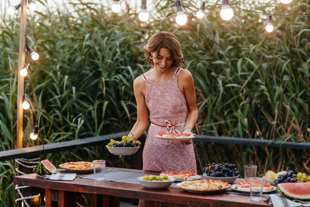 Beautiful woman setting up the table for outdoor dinner party.