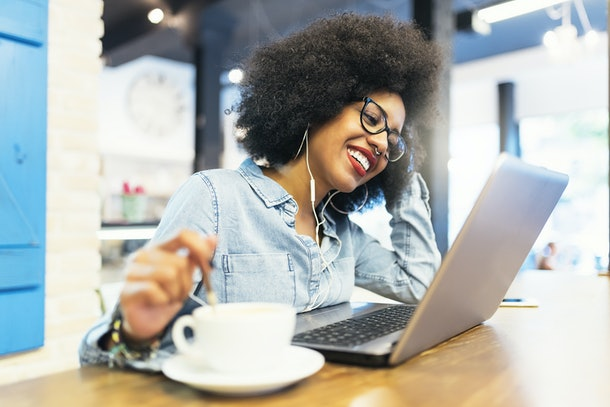 Beautiful afro american woman using mobile and laptop in the coffee shop. Communication concept.