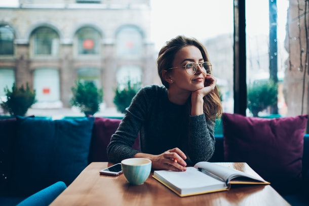 Dreaming beautiful hipster girl looking away while resting at cafeteria and writing romantic essay, attractive young woman in eyeglasses enjoying free time and planning to do list in notebook