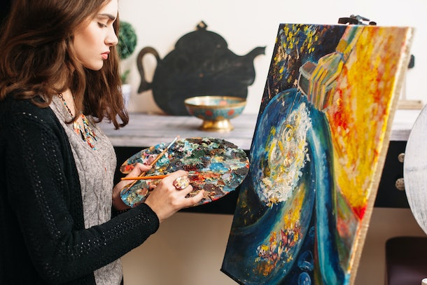 Creative contemporary painter paints a colorful abstract painting. Closeup of painting process in art workshop. Creative positive woman painter paints in her studio colorful abstract painting