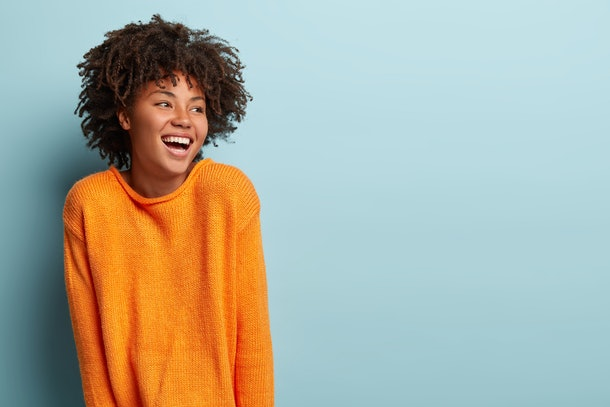 Glad overemotive dark skinned lady with curly hairstyle, laughs happily, expresses sincere emotions, being amused by friend, dressed in orange casual jumper, models in studio alone with mockup space