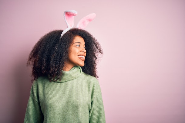 A woman wearing Easter bunny ears smiles in front of a pink wall.