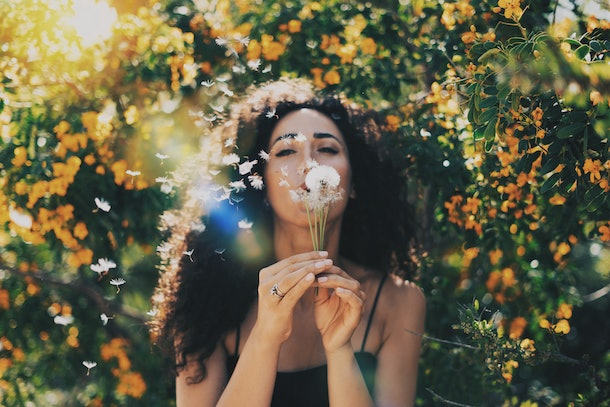 A woman blows out a dandelion in front of orange flower bushes on a sunny day.