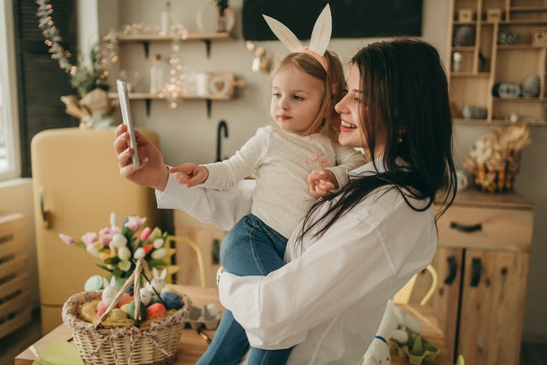A woman holds her daughter while taking a selfie in the kitchen on Easter Sunday.