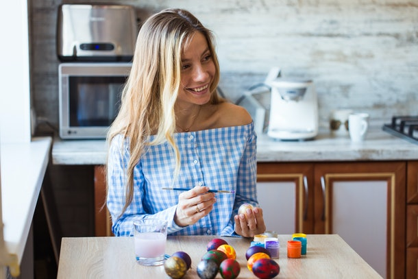 A woman with long blonde hair smiles while decorating Easter eggs in her kitchen.