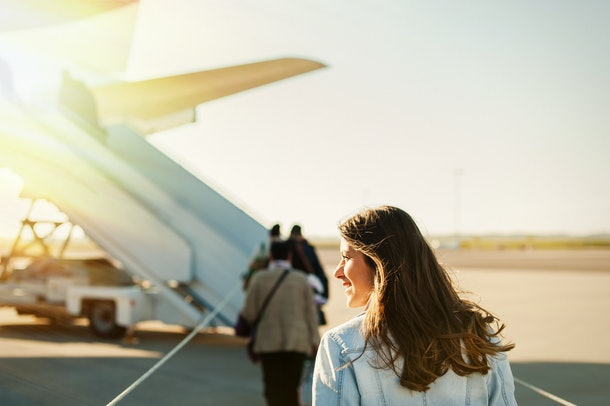 A woman in a denim jacket, boards her airplane from the tarmac.