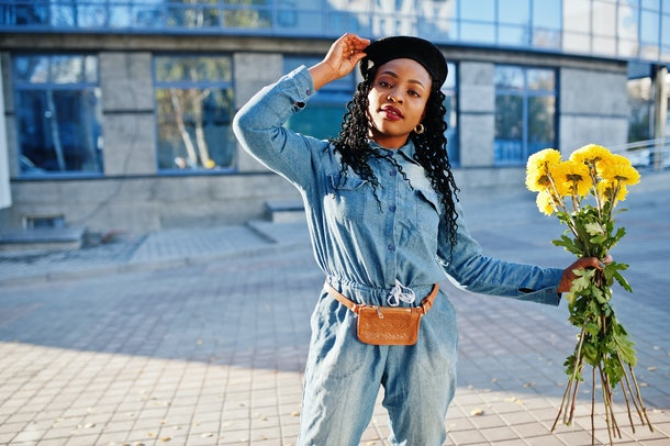 A stylish woman wearing a denim jumpsuit and leather fanny pack holds a bouquet of yellow flowers.
