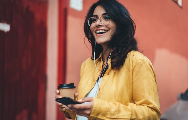 Happy girl in hipster eyeglasses listening to music while going to work, cheerful hispanic woman drinking coffee outdoors using modern smartphone device, happy smiling european businesswoman walking