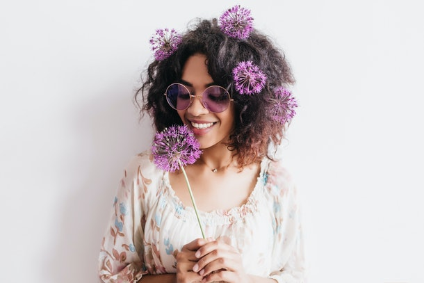 A woman with brown curly hair with purple flowers sticking out of it smiles while she holds a purple flower.