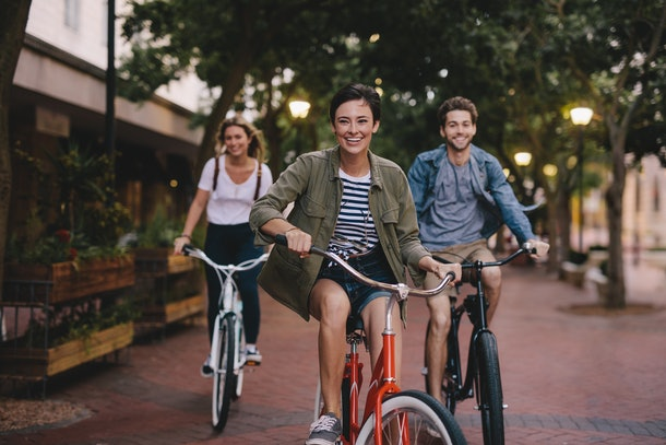 Three happy best friends ride bicycles down a street.