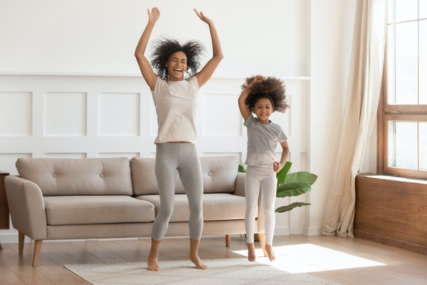 A happy woman dances with her niece in a bright living room.